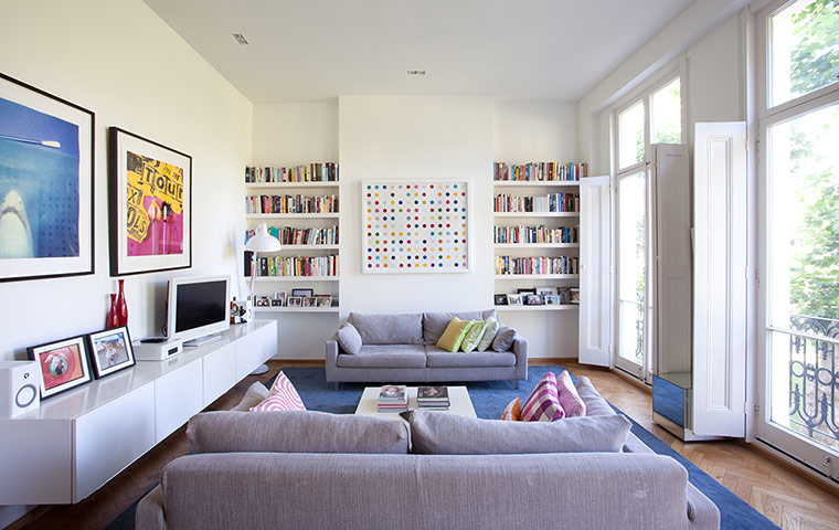 Living room with paintings on white walls and a grey sofa